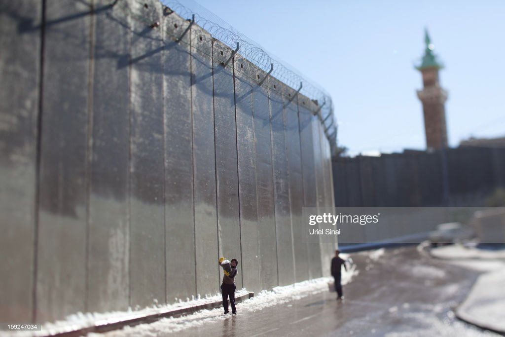 Image was created using a variable planed lens) Palestinian children play with snow in front of the controversial Israeli separation barrier on January 10, 2013 in the West Bank village of Abu Dis, at outskits of Jerusalem.