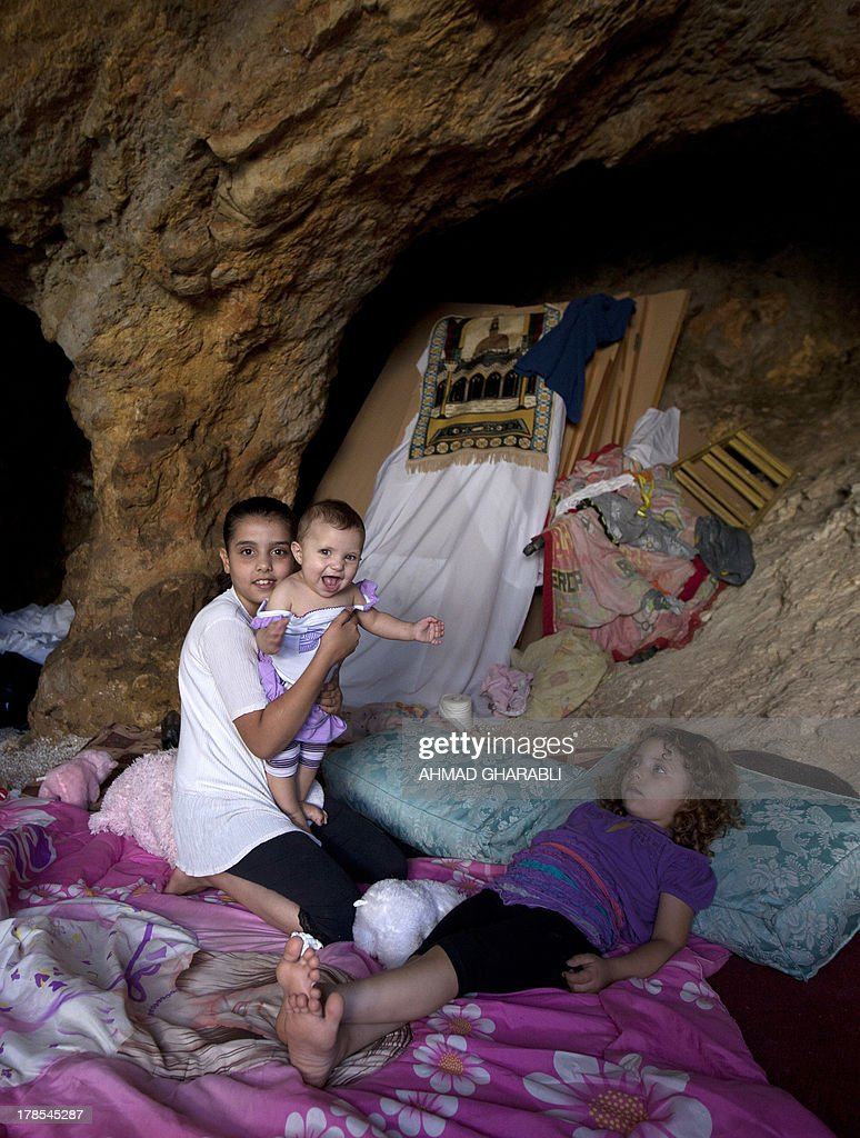 DAVISON - Palestinian children pose on a makeshift bed in the cave that hosts their family since the demolition of their house by Israeli forces on August 29, 2013 in the east Jerusalem neighborhood of Silwan. Israeli forces have destroyed the homes of 716 Palestinians in 2013, according to HRW, which has recorded a three-fold increase in the number of demolitions in east Jerusalem since last year. AFP PHOTO/AHMAD GHARABLI