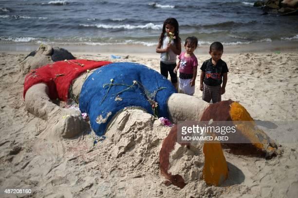 Palestinian children put flowers on a sand sculpture depicting Syrian boy Aylan Kurdi a threeyearold boy who drowned off Turkey on September 7 on...