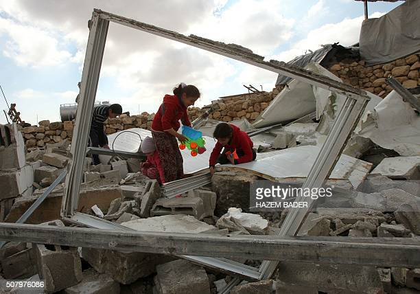 TOPSHOT Palestinian children search for toys in the remains of their home after it was demolished by Israeli bulldozers in a disputed military zone...