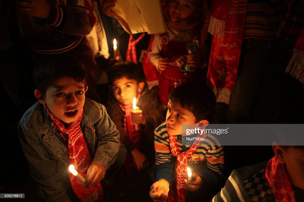 Palestinian children shout slogans to resolve Gaza power crisis while they hold candles and banners during a protest organized by the Democratic...
