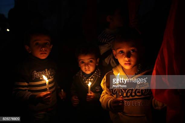 Palestinian children shout slogans to resolve Gaza power crisis while they hold candels and banners during a protest organized by the Democratic...