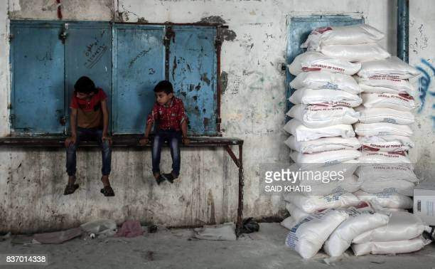 TOPSHOT Palestinian children sit by sacks of food aid provided by the United Nations Relief and Works Agency for Palestine refugees in the town of...