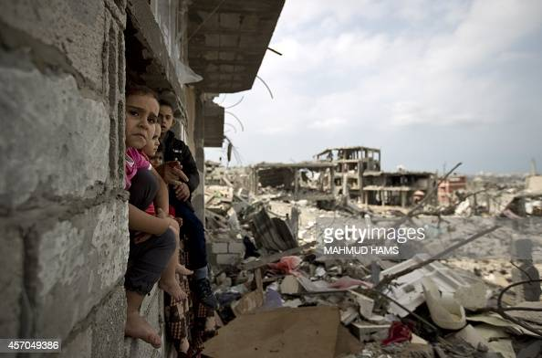Palestinian children sit on the window of a partially destroyed building in alTufah east of Gaza City on October 11 ahead of a donors conference in...