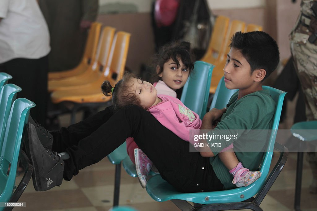 Palestinian children sit with their family (unseen) as they wait to cross into Egypt at the Rafah crossing terminal in the southern Gaza Strip on the border with Egypt on October 22, 2013. Hundreds of patients, students and foreign residents from the Palestinian side have rushed to the Rafah crossing after the Egyptian announcement of re-opening it for 6 days.