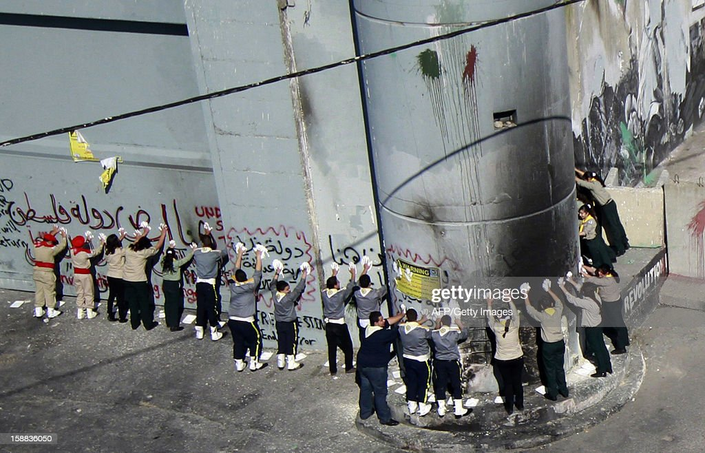 Palestinian children stamp their hand prints on the Israeli built controversial separation barrier as they take part in the 'Project Peace on Earth' activity to send out a message of peace at the main entrance of the West Bank town of Bethlehem on New Year's eve on December 31, 2012.