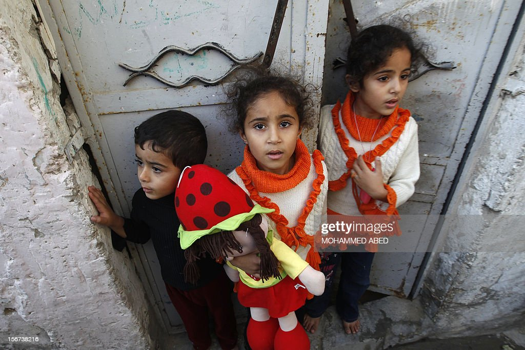 Palestinian children stand at the gate of their home as they watch the funeral procession of killed members of the Hejazi family, including two young children, in Beit Lahia, in the northern Gaza Strip on November 20, 2012, following an Israeli air strike the Hamas Health Ministry said. AFP PHOTO/MOHAMMED ABED