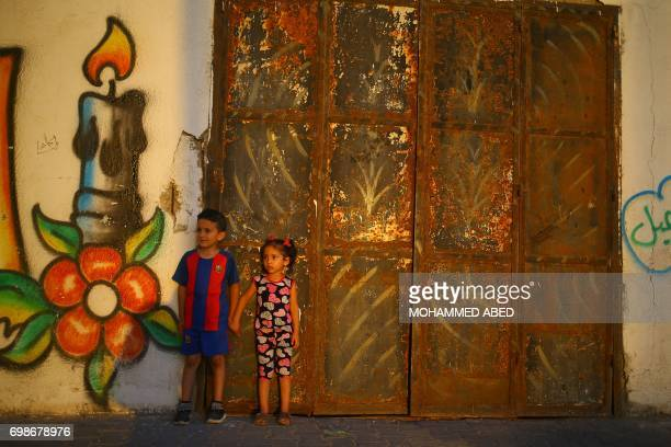 Palestinian children stand in front of a mural as the sun sets on June 20 in Gaza City during the Muslim holy month of Ramadan / AFP PHOTO / MOHAMMED...