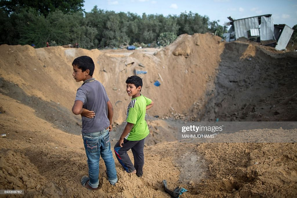 Palestinian children stand next to a crater on August 22 2016 in Beit Lahia in the northern Gaza Strip following an Israeli airstrike the day before...