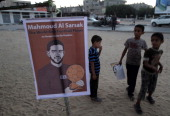 Palestinian children stand next to a picture of Palestinian football player Mahmoud Sarsak who has been held in Israeli jail since 2009 during a...