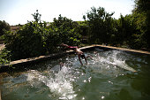 Palestinian children swimming in a water canal for irrigating crops in the West Bank village of Falamia near the city of Qalqilya This is one of few...
