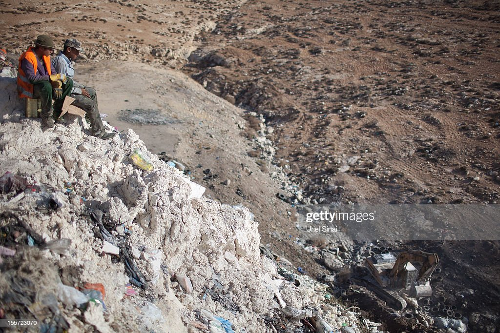 Palestinian children take a break as they sift through a garbage dump on November 7, 2012 south of Hebron, West Bank. About 40 Palestinain men and children work at the West Bank garbage dump looking for clothing, metal and wood discarded, in large part, from the Jewish settelment in the region.