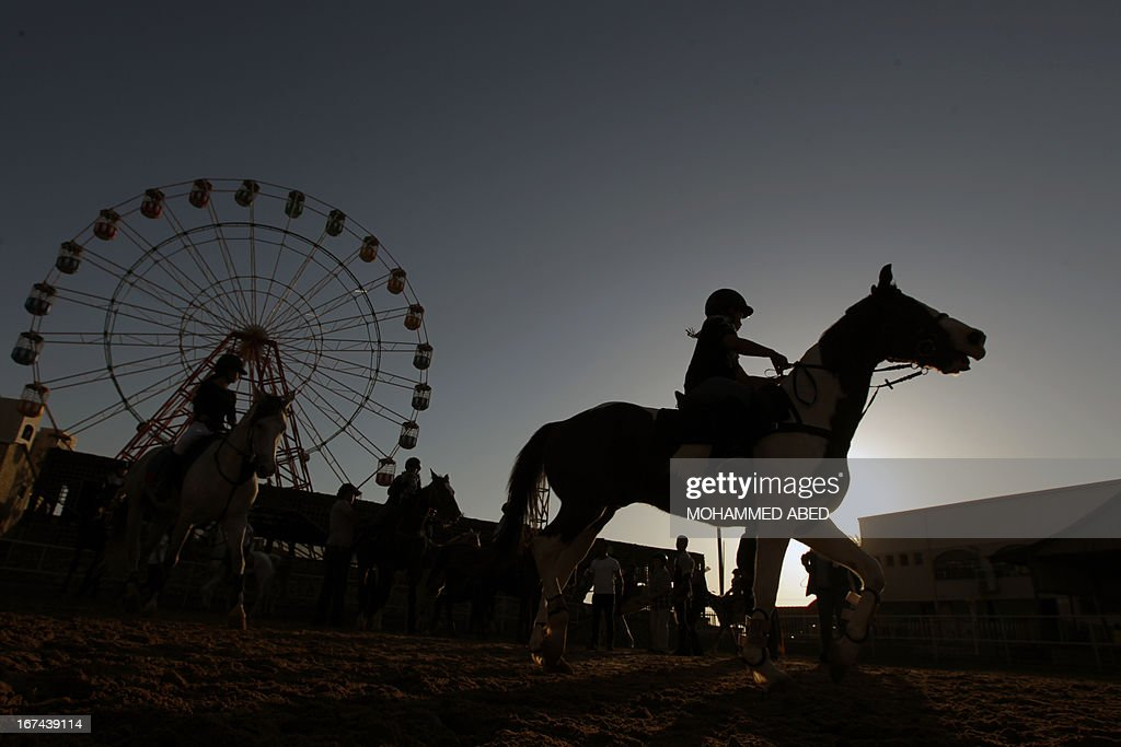 Palestinian children take a horse riding lesson on April 25, 2013 in Beit Lahia, northern of Gaza Strip.