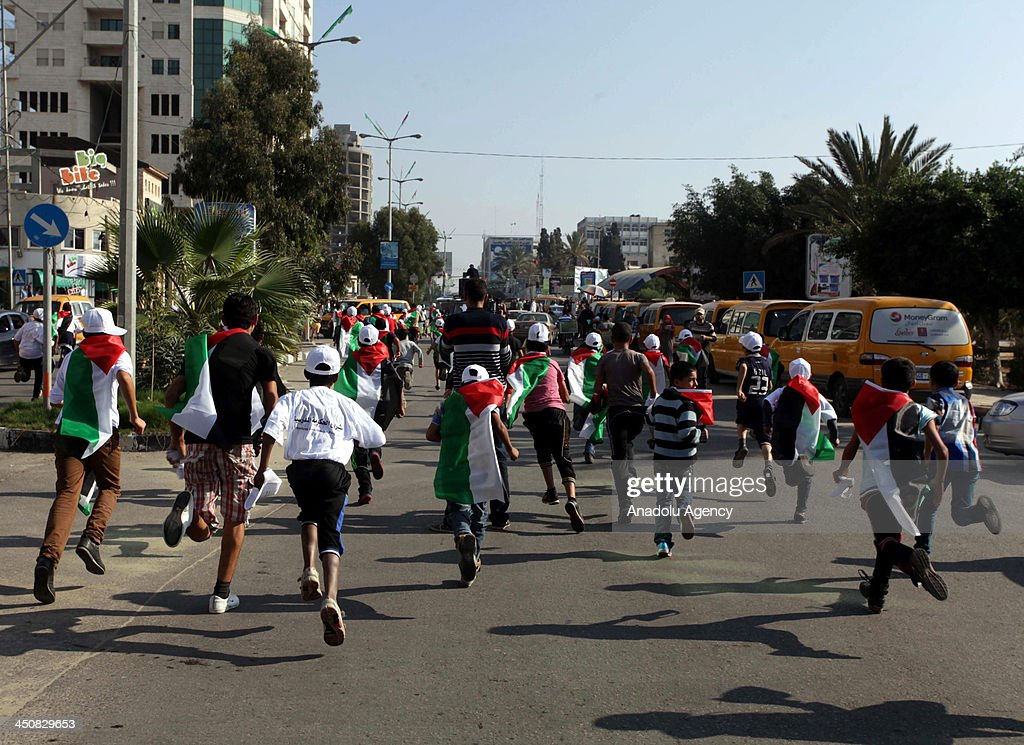 Palestinian children take part in a marathon, marking 'Universal Children's Day' in Gaza City on November 20, 2013. Around 200 children participated in the marathon calling for peace and end the blockade on Gaza Strip.