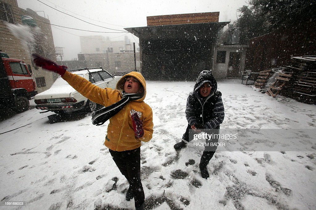 Palestinian children throw snowball as snow falls over the village of Halhoul, near the West Bank town of Hebron, on January 9, 2013. Extreme weather, including torrential rains and heavy winds, killed four people in Israel and the Palestinian territories on January 8, as widespread flooding swept the Middle East. AFP PHOTO / HAZEM BADER