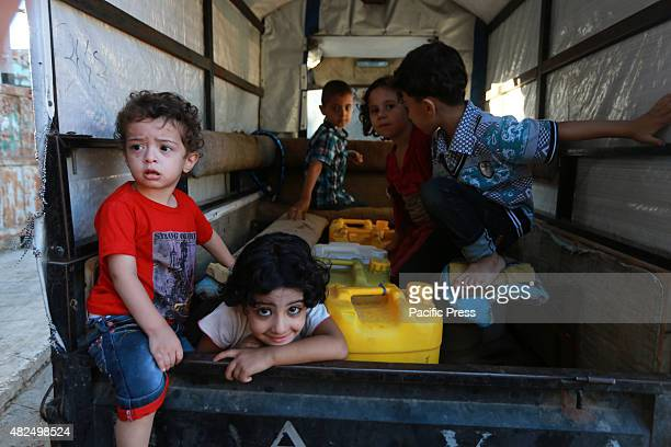 Palestinian children together with their plastic bottles and jerry cans with drinking water from a public tap in the southern Gaza Strip refugee camp...