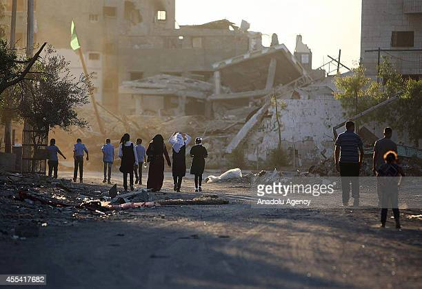 Palestinian children walk on a street heading to school in Gaza City Gaza on September 14 2014 on the first day of the new school year Half a million...