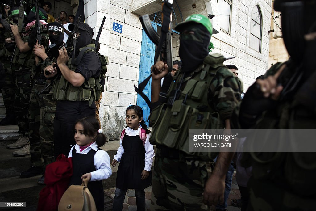 Palestinian children walk past militants of Hamas' armed wing, the Ezzedine al-Qassam Brigades, during the funeral procession of one of their leaders, Judah Shamallah, in Gaza City on November 24, 2012, who died overnight from injuries he endured from the week-long confrontation between Israel and Gaza militants. A ceasefire came into effect on November 21, in and around Gaza after a week of cross-border violence that killed at least 160 people.
