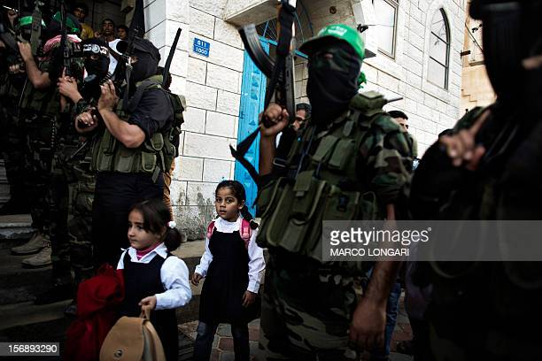 Palestinian children walk past militants of Hamas' armed wing the Ezzedine alQassam Brigades during the funeral procession of one of their leaders...