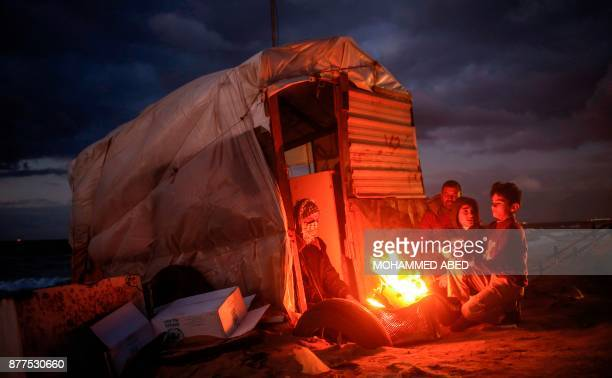 TOPSHOT Palestinian children warm up around a fire by a shack along the beach in Gaza City on November 22 2017 / AFP PHOTO / MOHAMMED ABED