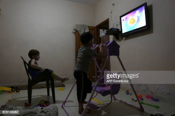 Palestinian children watch television during the few hours of mains electricity supply they receive every day on July 31 at Rafah refugee camp in the...