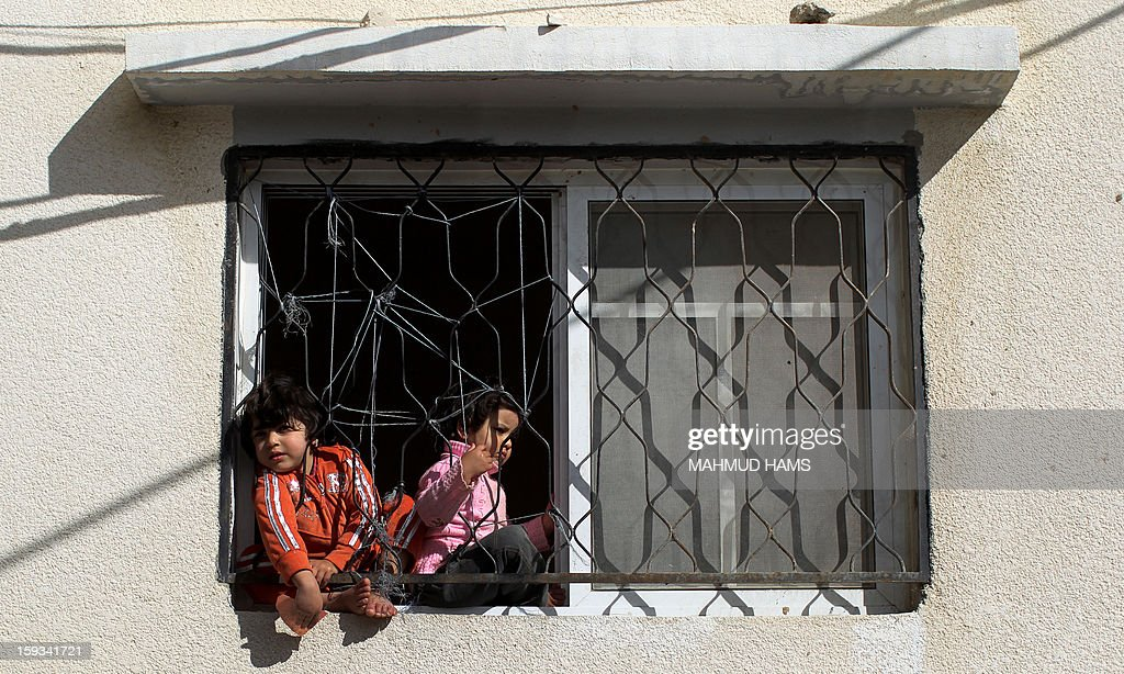 Palestinian children watch the funeral procession of Anwar Mohammed al-Mamluk from their home in Gaza City on January 12, 2013. Israeli soldiers shot dead Mamluk and wounded another in the northern Gaza Strip, a spokesman for the territory's emergency services said. AFP PHOTO/MAHMUD HAMS