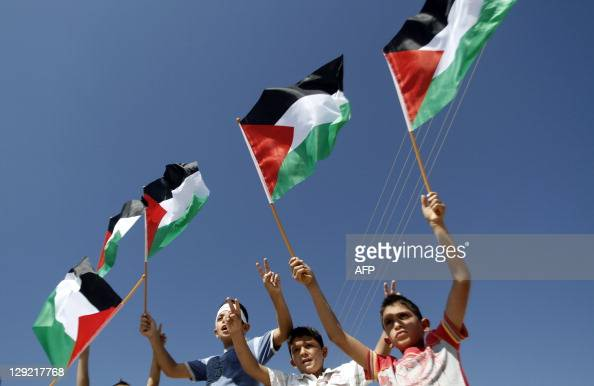 Palestinian children wave their national flag during a demonstration against Israel's separation barrier and in solidarity with Palestinian prisoners...