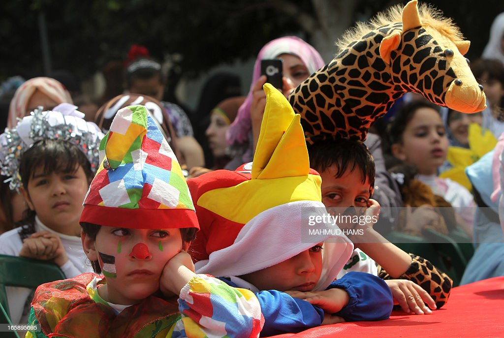 Palestinian children wear costumes during the Children's Fund festival at the Community College of the Islamic University of Gaza in Gaza city on April 7, 2013. AFP PHOTO MAHMUD HAMS