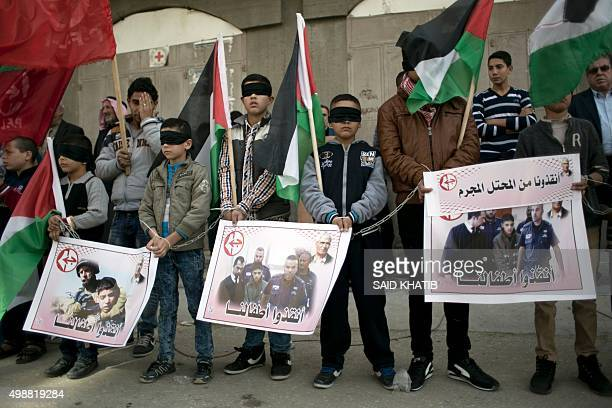 Palestinian children wearing blindfolds and waving the national flag take part in a demonstration calling for the release of Palestinian children...
