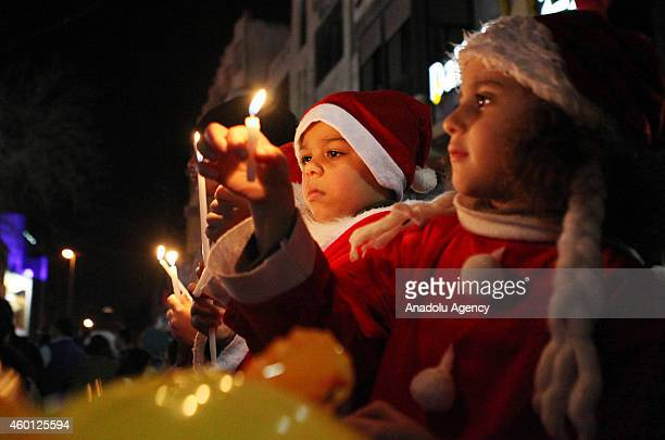 Palestinian children wearing Santa Claus costumes light candles for peace near a Christmas tree ornamented with lights at the Yasser Arafat square in...