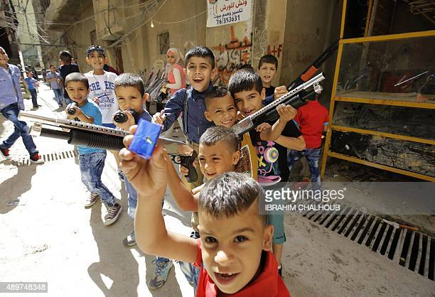 Palestinian children who fled the Yarmuk refugee in the Syrian capital Damascus play with toy guns during the Eid alAdha holiday in the Baddawi...