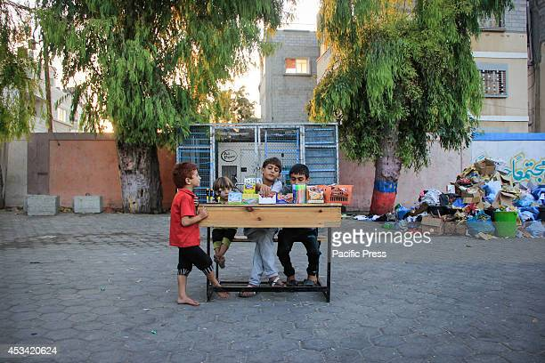 Palestinian children who fled to UNRWA schools because of the fighting between the Israeli army and the Palestinian resistance they sell sweets to...