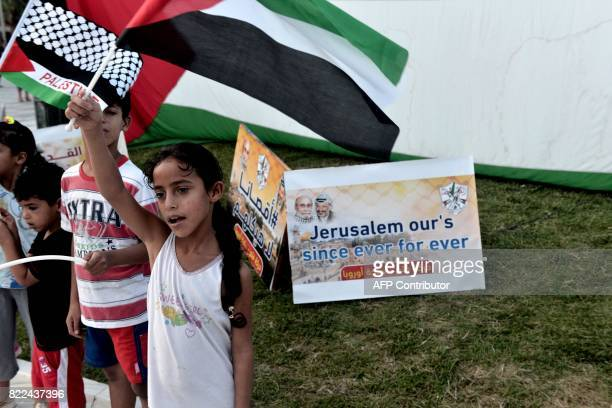 Palestinian children who live in Greece stand next to a placard reading 'Jerusalem our's since ever for ever' during a demonstration against the...