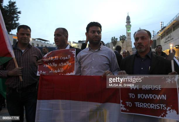 Palestinian Christian and Muslim men hold placards during a gathering in the West Bank town of Bethlehem on April 10 2017 in solidarity with the...