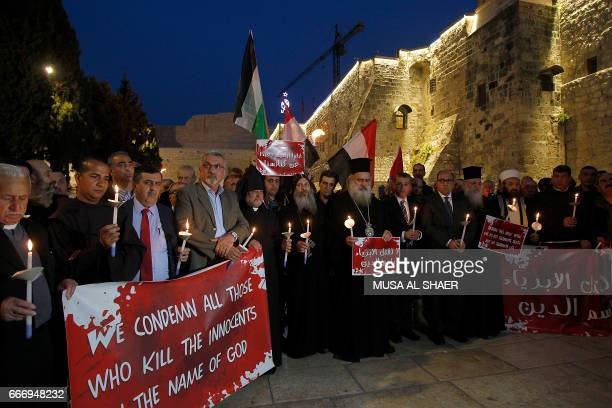 Palestinian Christian and Muslim religious leaders hold candles during a gathering in the West Bank town of Bethlehem on April 10 2017 in solidarity...