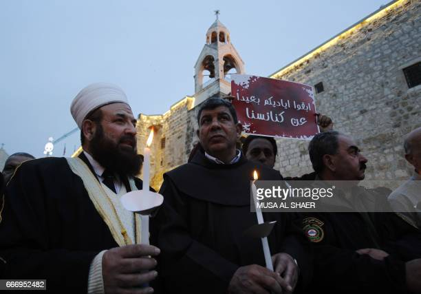Palestinian Christians and Muslims clergymen hold candles during a gathering in the West Bank town of Bethlehem on April 10 2017 in solidarity with...