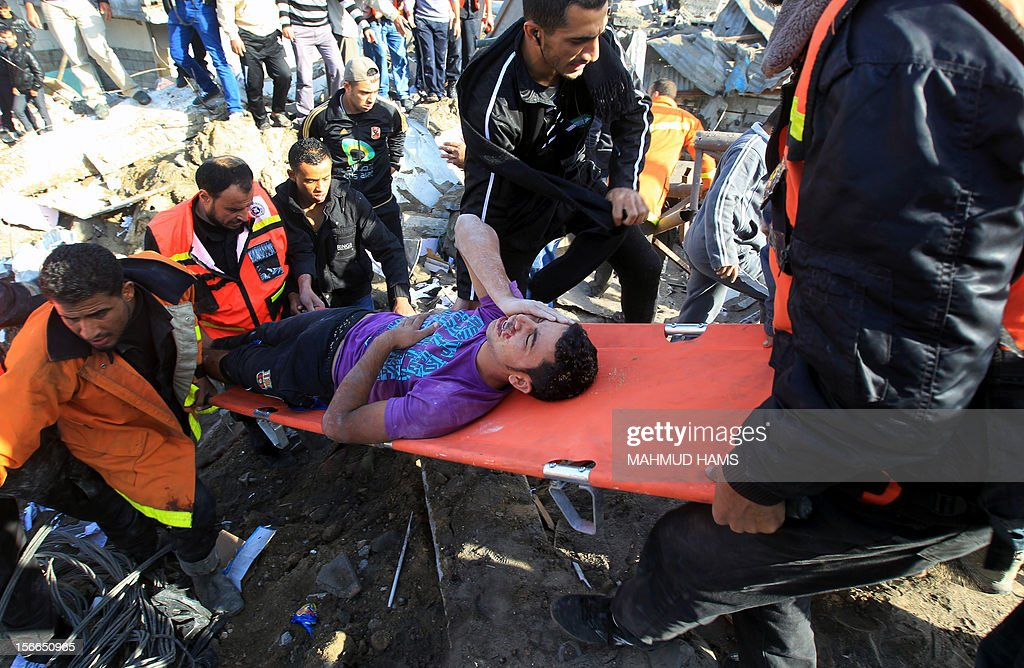 Palestinian civil defence staff carry a survivor on a stretcher after he was pulled out from under the rubble of a destroyed house following an Israeli air strike on Gaza City on November 18, 2012. Fresh Israeli air strikes hit a Gaza City media centre and homes in northern Gaza in the early morning, as the death toll mounted, despite suggestions from Egypt's President Mohamed Morsi that there could be a 'ceasefire soon.'
