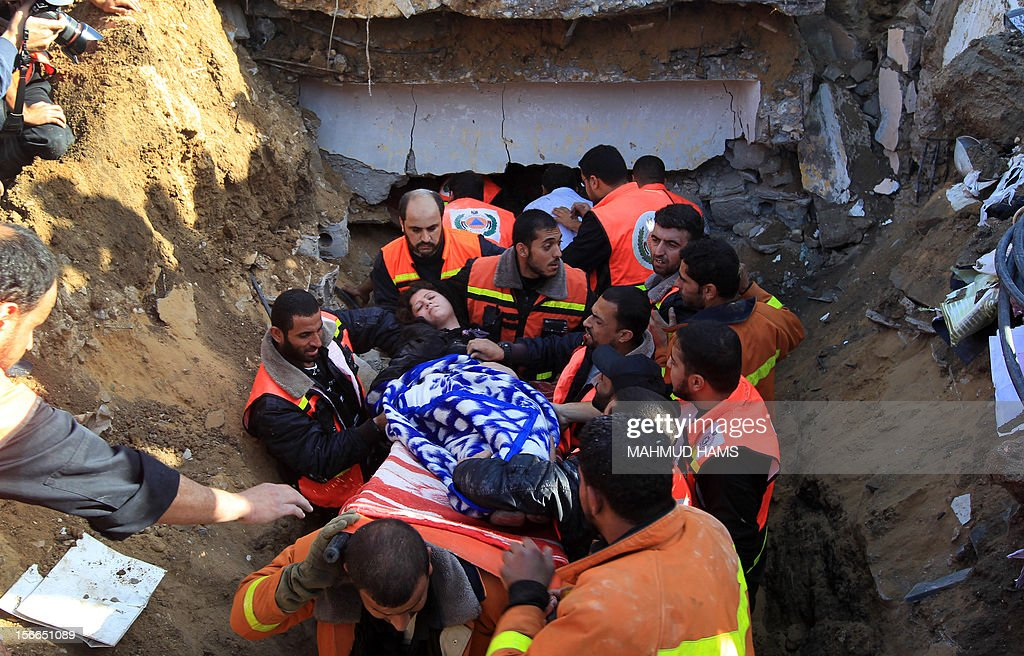 Palestinian civil defence staff carry a survivor on a stretcher after she was pulled out from under the rubble of a destroyed house following an Israeli air strike on Gaza City on November 18, 2012. Fresh Israeli air strikes hit a Gaza City media centre and homes in northern Gaza in the early morning, as the death toll mounted, despite suggestions from Egypt's President Mohamed Morsi that there could be a 'ceasefire soon.' AFP PHOTO/MAHMUD HAMS