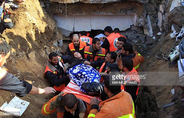 Palestinian civil defence staff carry a survivor on a stretcher after she was pulled out from under the rubble of a destroyed house following an...
