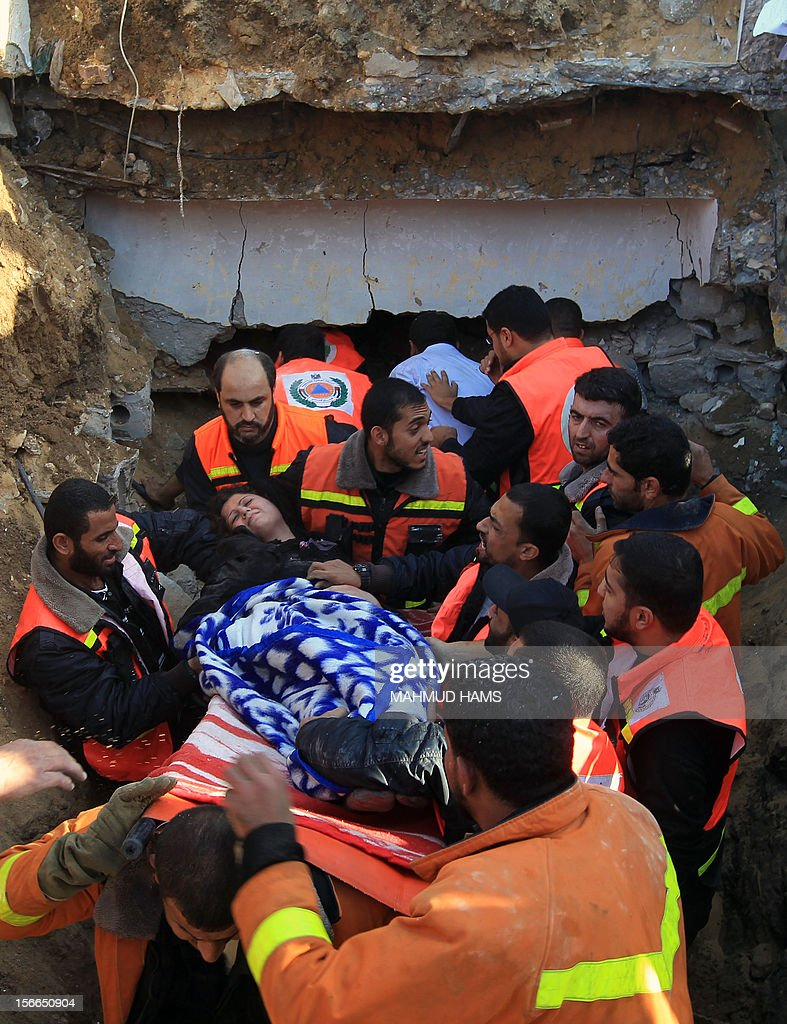 Palestinian civil defense staff carry a survivor on a stretcher after she was pulled out from under the rubble of a destroyed house after an Israeli air strike on Gaza City on November 18, 2012. Fresh Israeli air strikes hit a Gaza City media centre and homes in northern Gaza in the early morning, as the death toll mounted, despite suggestions from Egypt's President Mohamed Morsi that there could be a 'ceasefire soon.' AFP PHOTO/MAHMUD HAMS