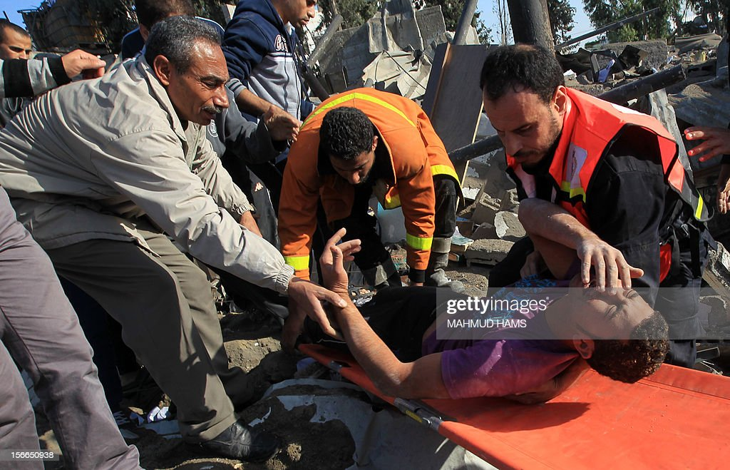 Palestinian civil defense staff carry a survivor on a stretcher after he was pulled out from under the rubble of a destroyed house following an Israeli air strike on Gaza City on November 18, 2012. Fresh Israeli air strikes hit a Gaza City media centre and homes in northern Gaza in the early morning, as the death toll mounted, despite suggestions from Egypt's President Mohamed Morsi that there could be a 'ceasefire soon.' AFP PHOTO/MAHMUD HAMS