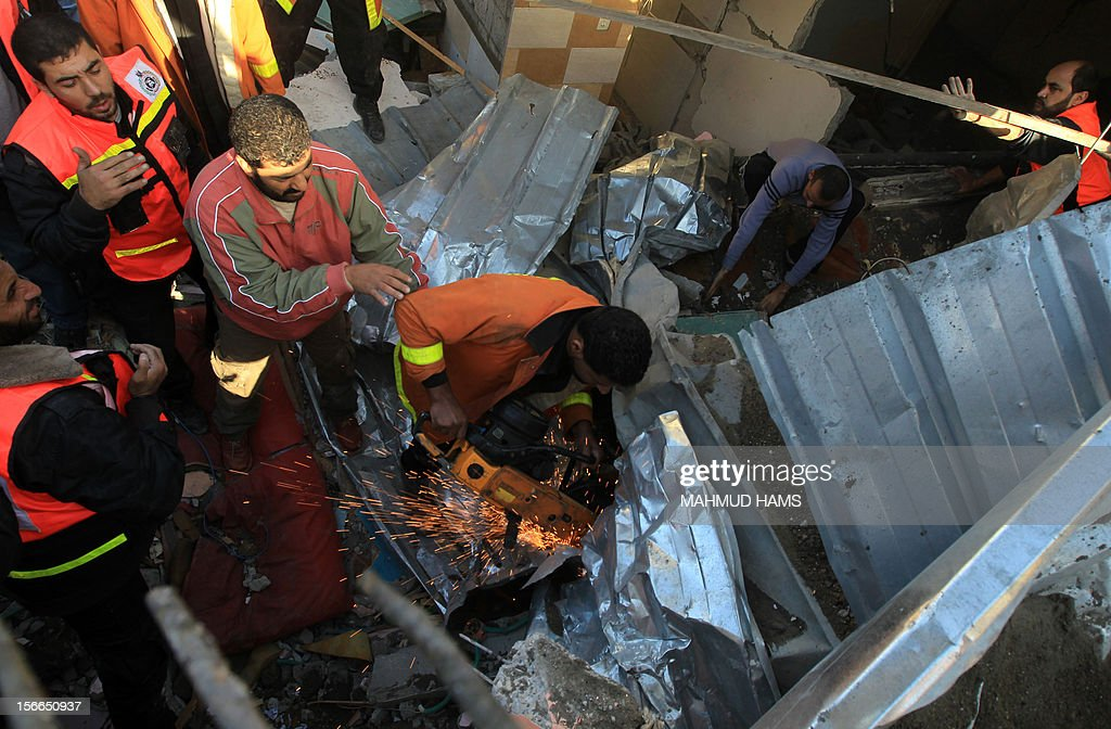 Palestinian civil defense staff use equipment to cut through metal as they search for victims stuck under the rubble of a destroyed house after it was damaged during an Israeli air strike on Gaza City on November 18, 2012. Fresh Israeli air strikes hit a Gaza City media centre and homes in northern Gaza in the early morning, as the death toll mounted, despite suggestions from Egypt's President Mohamed Morsi that there could be a 'ceasefire soon.'