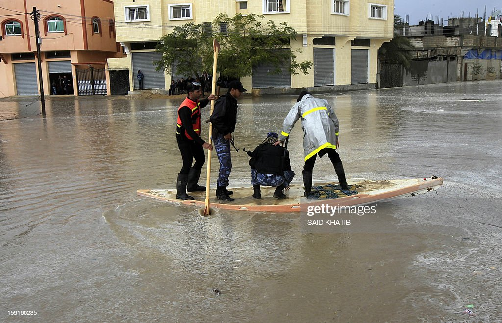 A Palestinian Civil Defense worker transports Hamas policemen using a stand-up kayak across a flooded street, in the Rafah refugee camp, in the southern Gaza Strip, on January 9, 2013. A storm has hit the eastern Mediterranean coast and heavy rains with flooding are forecast in Israel and the Palestinian territories for the next couple of days, with a good chance of snow falling in the higher elevations. AFP PHOTO / SAID KHATIB