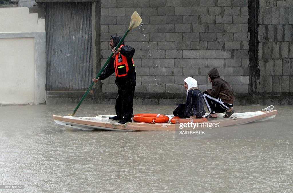 A Palestinian Civil Defense worker transports people on a stand up kayak along a flooded street in the Rafah refugee camp, in the southern Gaza Strip, on January 9, 2013. A storm has hit the eastern Mediterranean coast and heavy rains with flooding are forecast in Israel and the Palestinian territories for the next couple of days, with a good chance of snow falling in the higher elevations. AFP PHOTO / SAID KHATIB