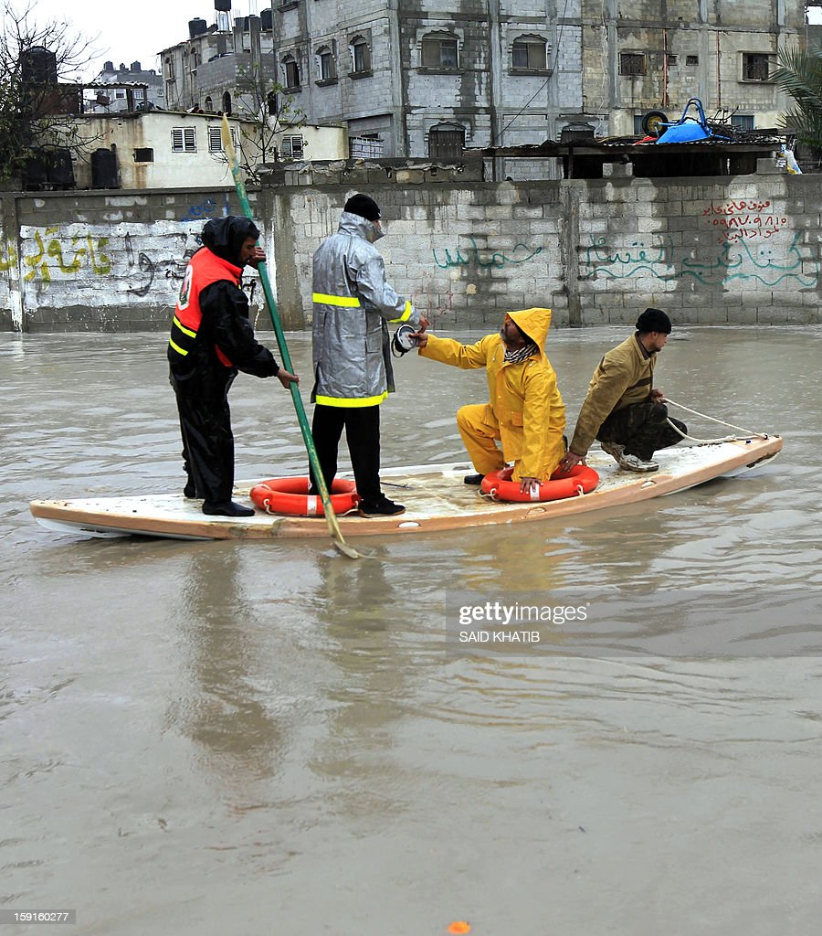 A Palestinian Civil Defense worker transports people using a stand-up kayak along a flooded street, in the Rafah refugee camp, in the southern Gaza Strip, on January 9, 2013. A storm has hit the eastern Mediterranean coast and heavy rains with flooding are forecast in Israel and the Palestinian territories for the next couple of days, with a good chance of snow falling in the higher elevations. AFP PHOTO / SAID KHATIB