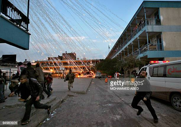 Palestinian civilians and medics run to safety during an Israeli strike over a UN school in Beit Lahia northern Gaza Strip early on January 17 2009 A...