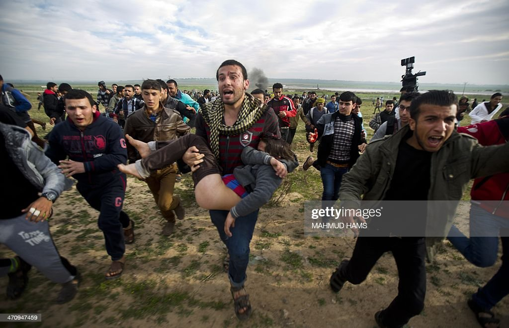 Palestinian civilians carry an injured boy during clashes with Israeli security forces near the eastern border of the Gaza Strip east of the northern...