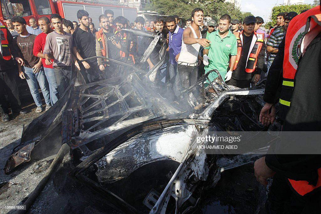 Palestinian civilians watch as firefighters extinguish fire from a car after it was hit by an Israeli air strike in Beit Lahia, northern of Gaza Strip, on November 19, 2012. Air strikes across the Gaza Strip killed 18 people, raising the Palestinian death toll to 95 on the sixth day of a relentless Israeli aerial campaign. AFP PHOTO/MOHAMMED ABED