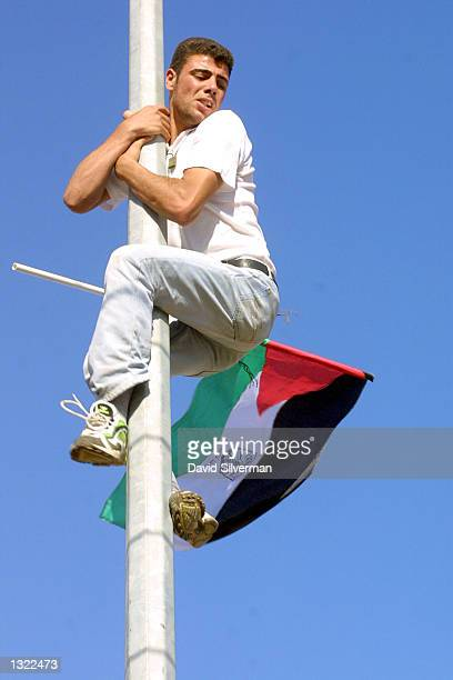 Palestinian climbs an electricity pole to raise his national flag during a demonstration protesting the Israeli occupation at an army roadblock July...
