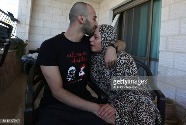 Palestinian clown Mohammad Abu Sakha kisses his mother at his family home in the West Bank city of Jenin following his release on August 31 2017 from...